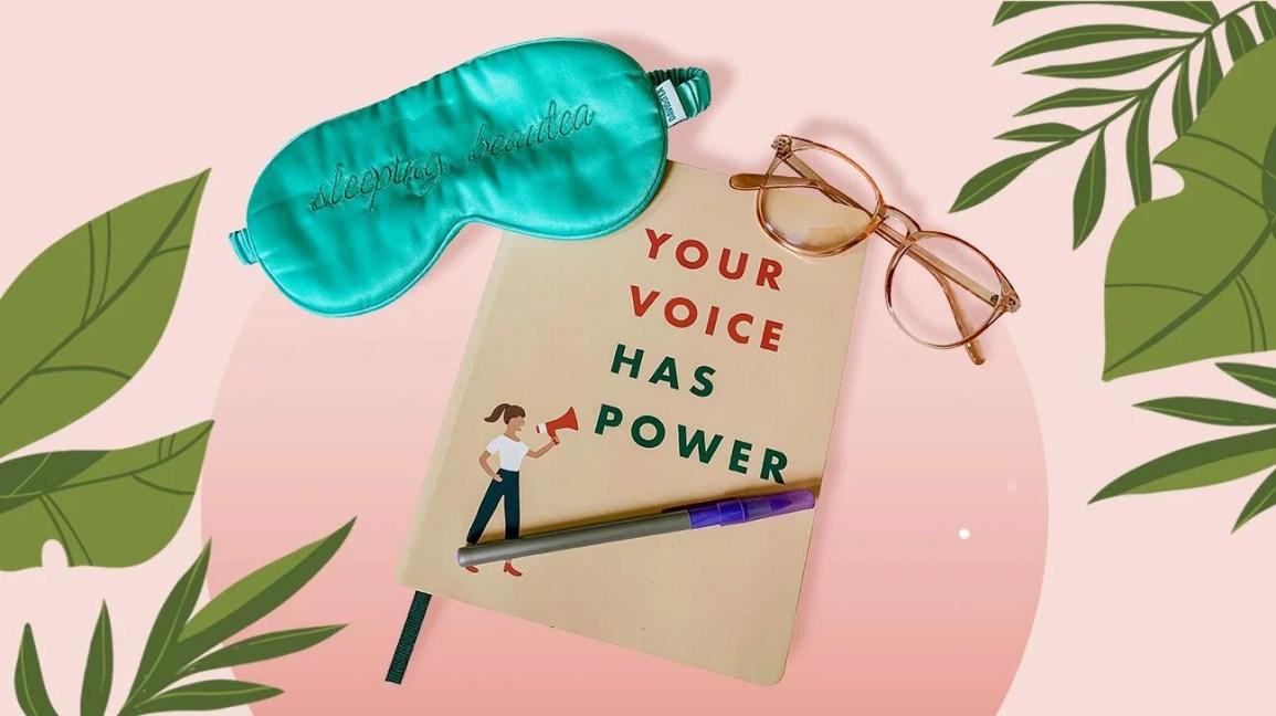 Suprimentos de autocuidado, incluindo diário, óculos de bloqueio de luz azul e máscara de dormir na frente de ilustração estilizada de folhas e fundo rosa claro