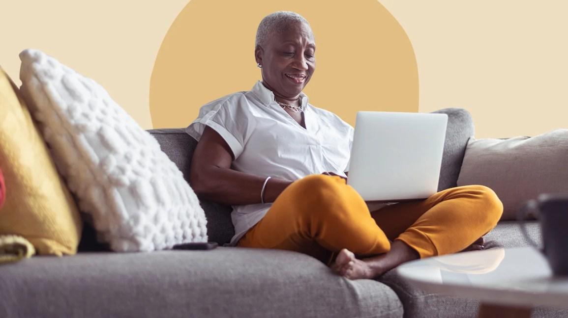 Mulher sentada no sofá olhando para o laptop