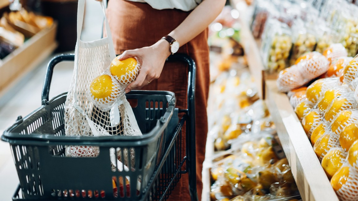 a person placing grapefruits in a shopping basket