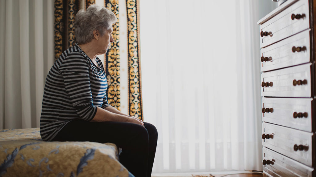 a senior woman with anxiety and dementia looking out of a window