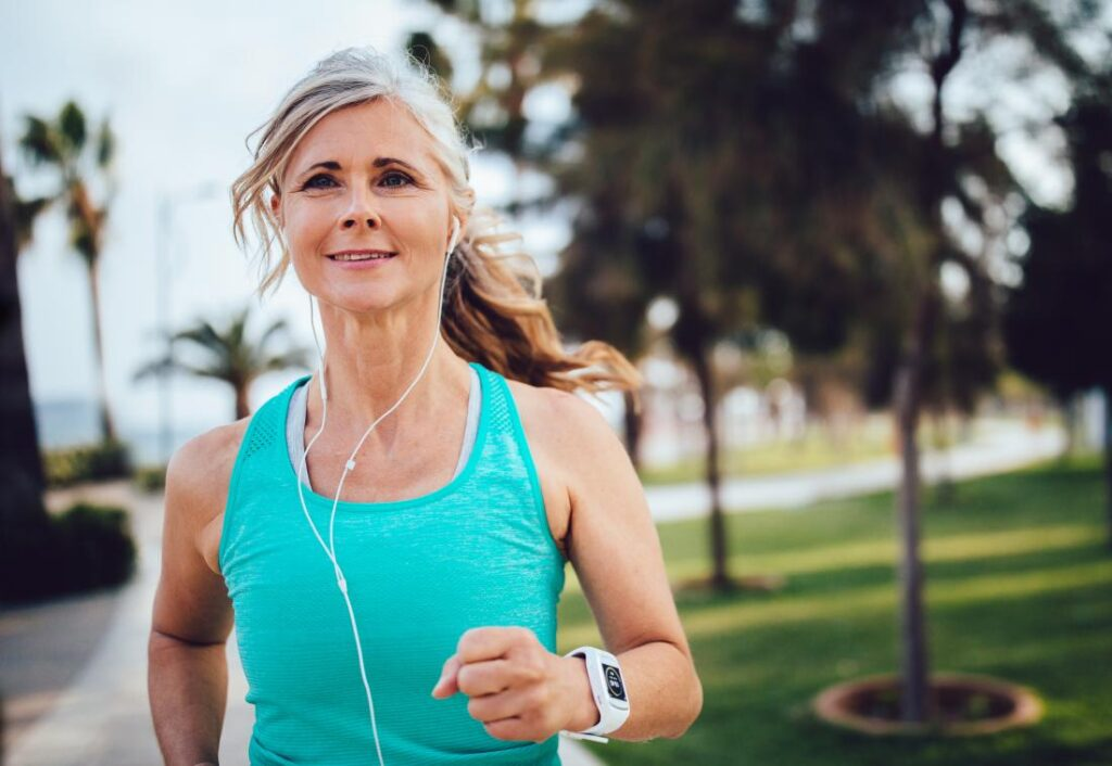woman jogging through park listening to headphones
