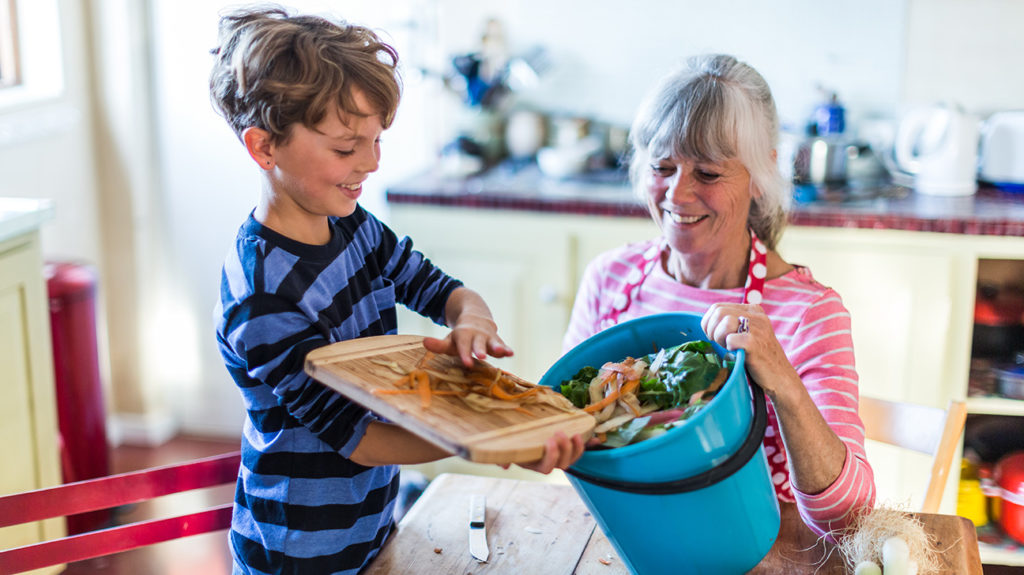 a young boy and adult woman putting food waste into a composting bin
