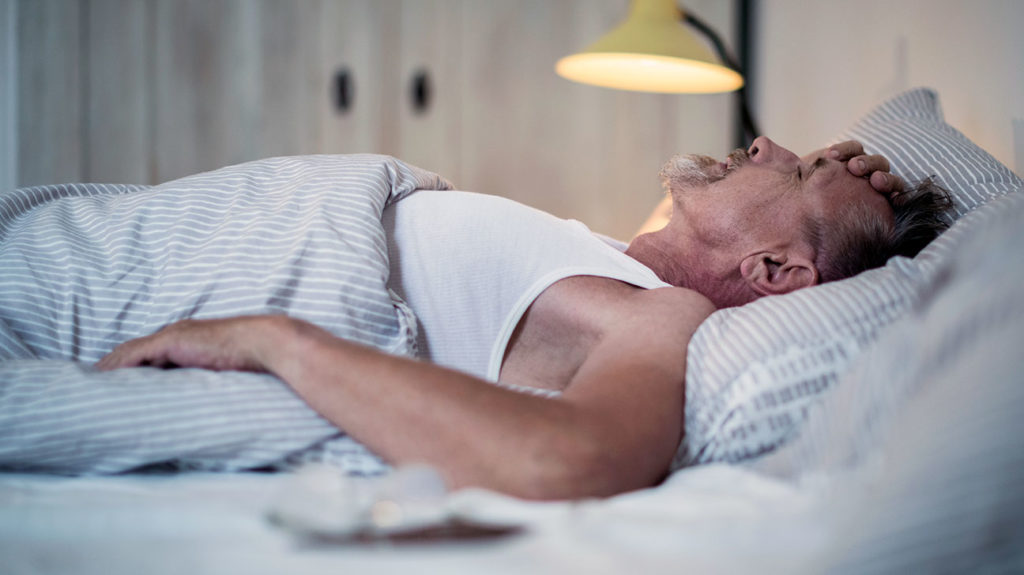 a man struggling to sleep because of sleep apnea  which may also cause his erectile dysfunction