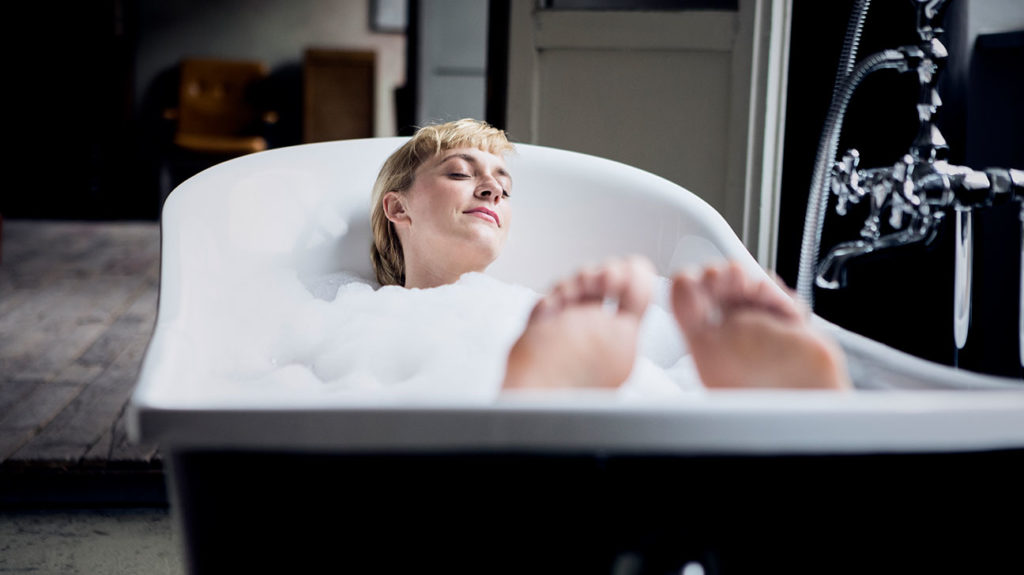 a woman having a warm bath to help treat hemorrhoids