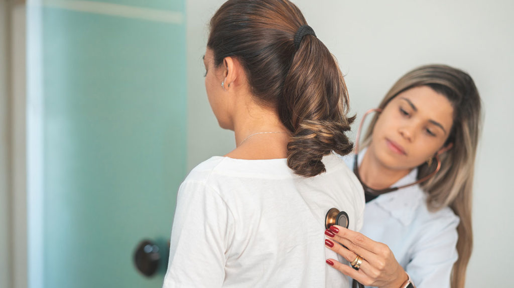 a pulmonologist checking a womans lung function with a stethoscope on her back