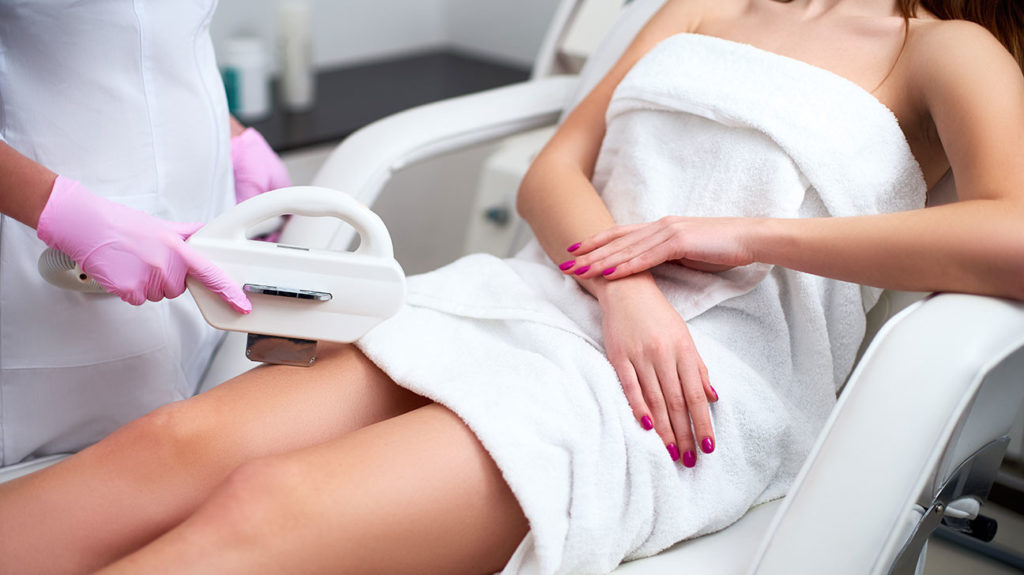 a woman having ipl treatment to remove hair from her leg