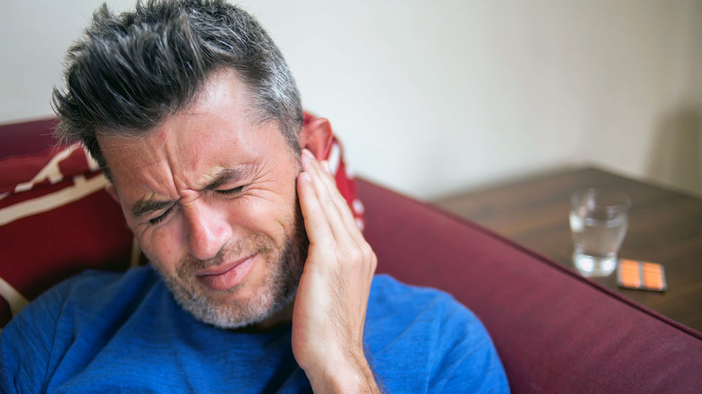 a man with ear pain due to an allergy