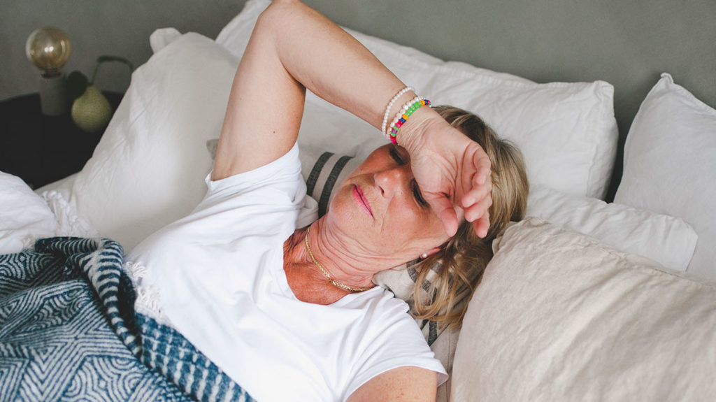 a woman struggling to sleep because she has heartburn at night