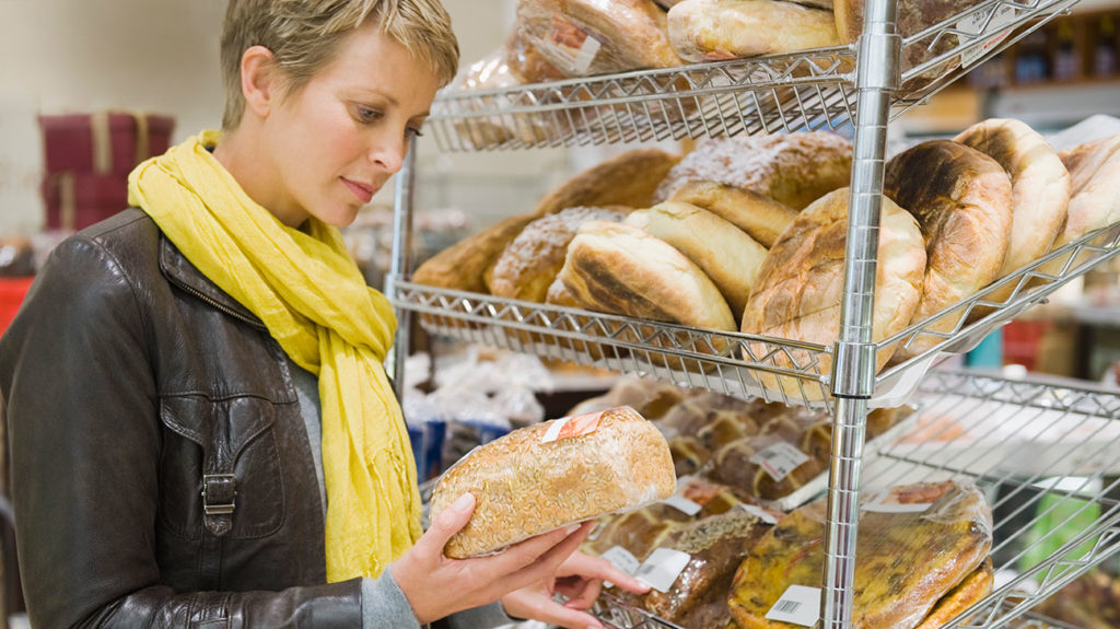 a woman looking at a load of bread that is high in refined carbs