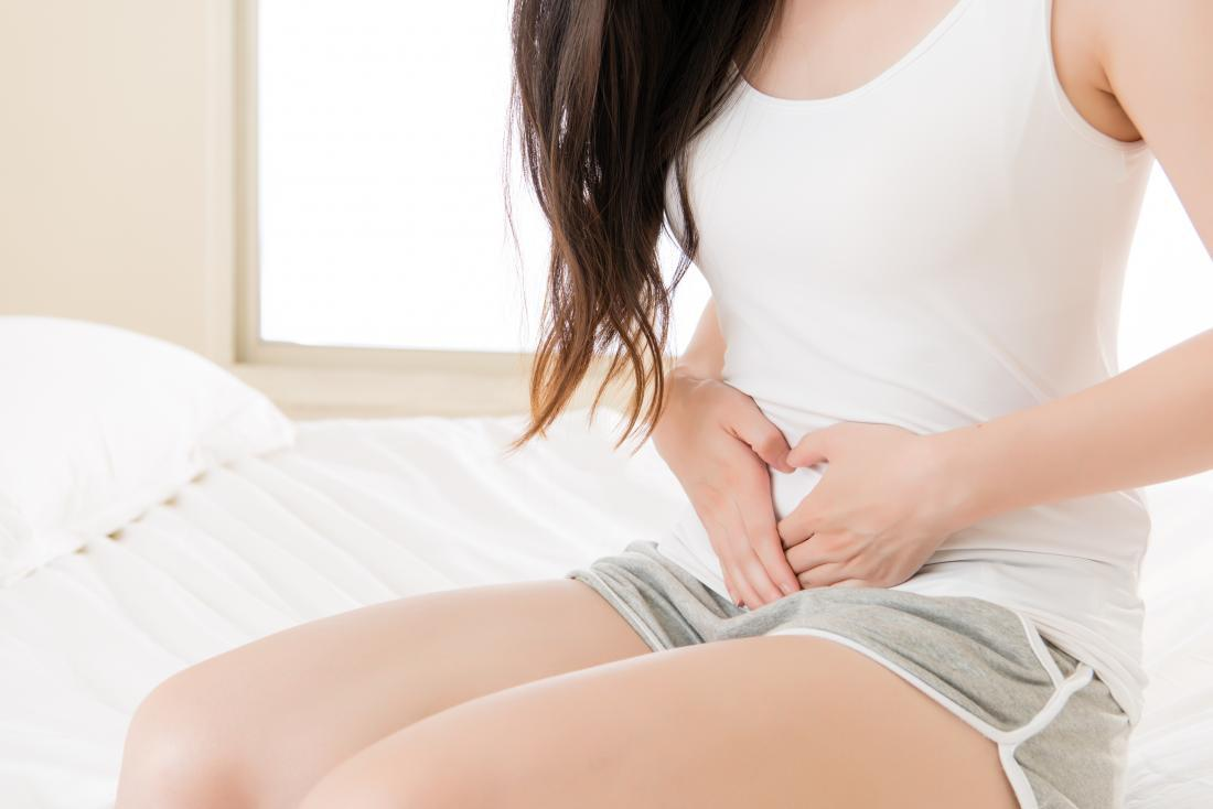 Girl sat on bed with stomach pain