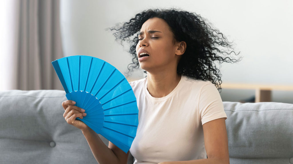 a woman fanning herself and wondering why she is always hot