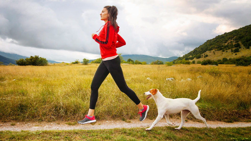a woman running with her dog as part of her routine to increase fitness and treat depression