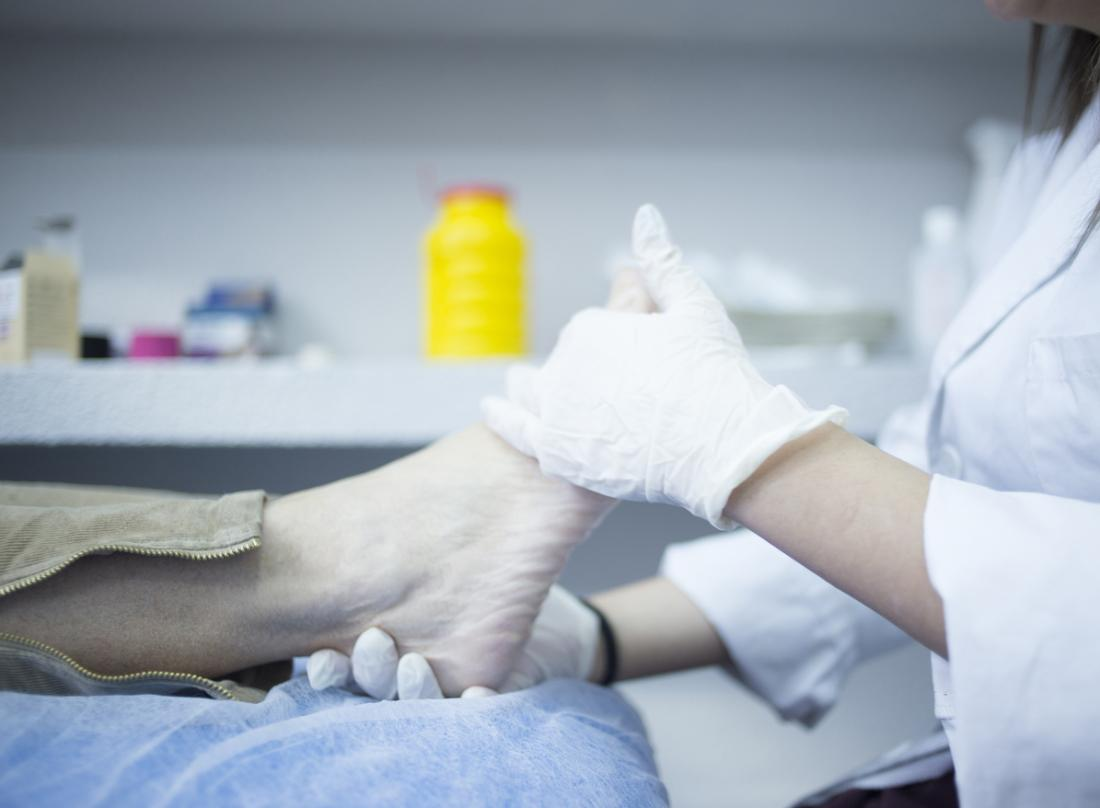 podiatrist inspecting patients foot