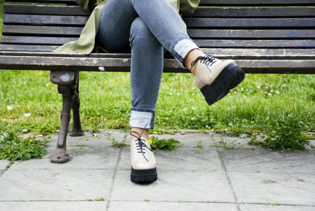 woman sat on a bench with her legs crossed which may cause numbness in legs and feet