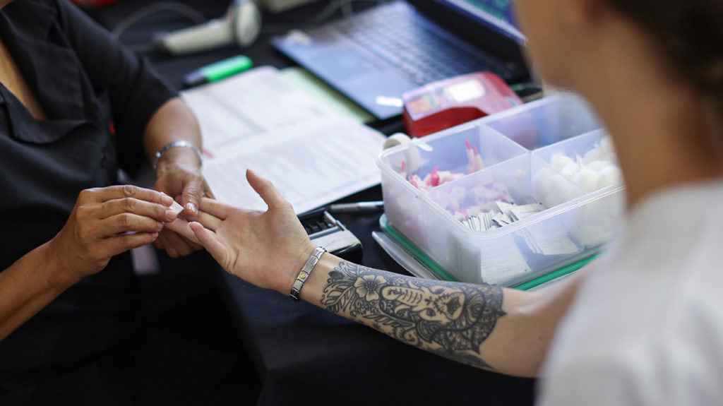 a woman with a tattoo giving blood
