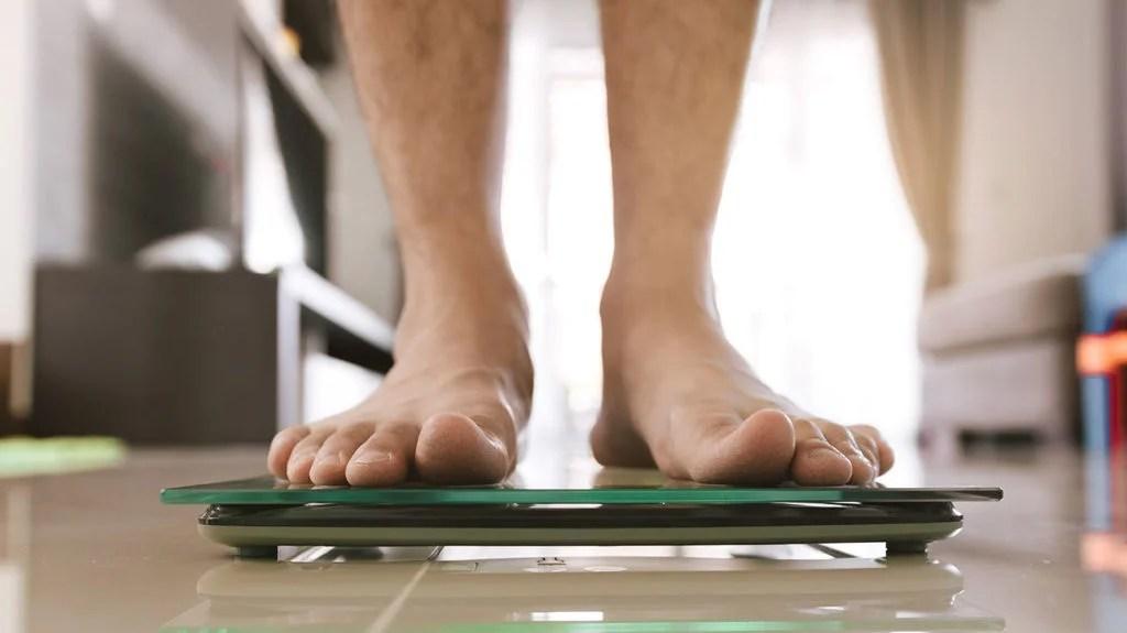 un homme se pesant et se demandant où il s'inscrit dans les statistiques d'obésité