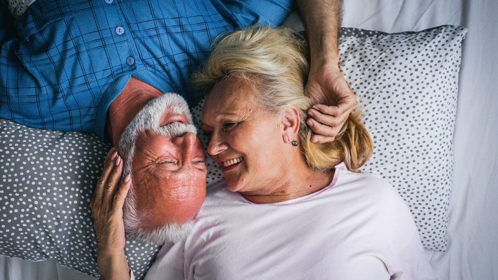 a senior couple lying in bed and thinking about Sex after menopause