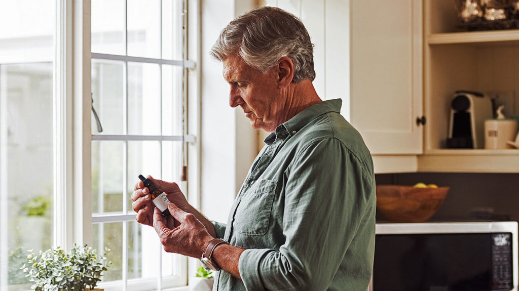 a man looking at some cannabidiol CBD oil