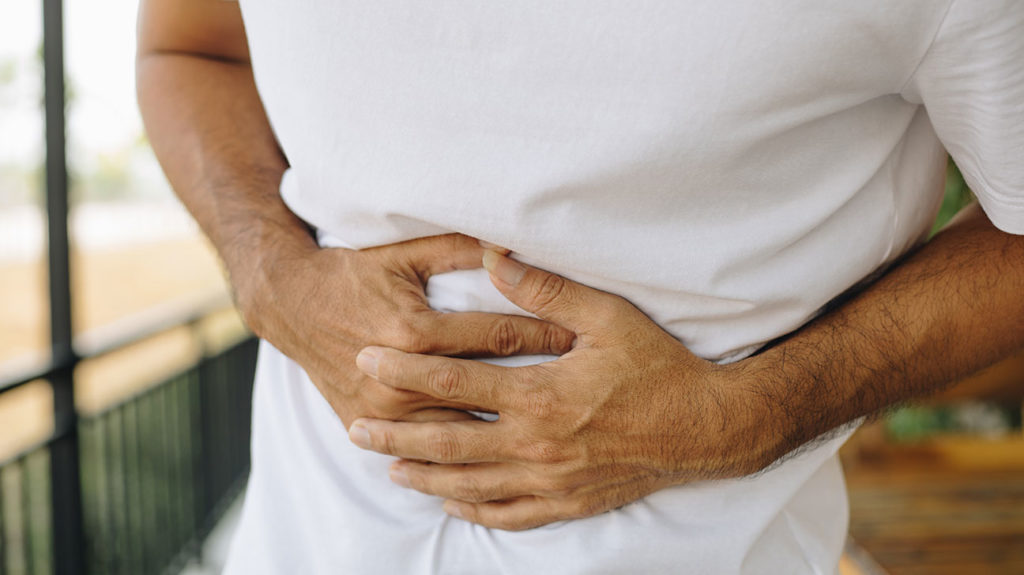 a man holding his stomach because of Gastrointestinal infection