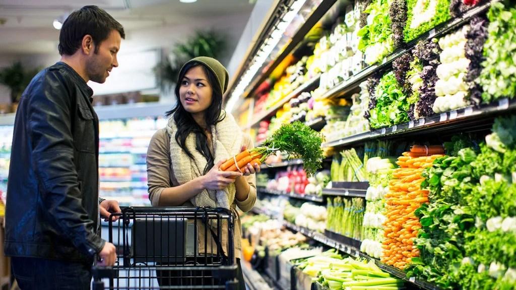 un couple dans un supermarché parle des micros vs macros dans leur nourriture