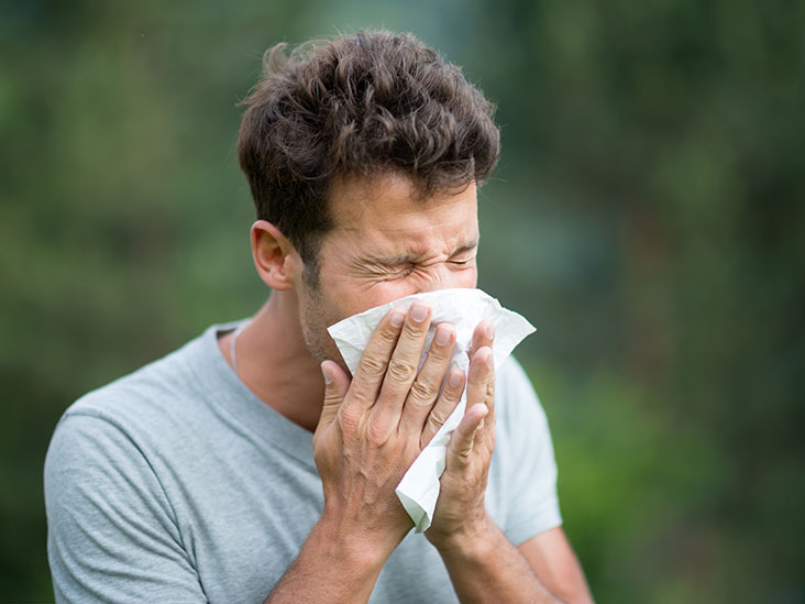 a man sneezing into a tissue to help stop the spread of coronavirus