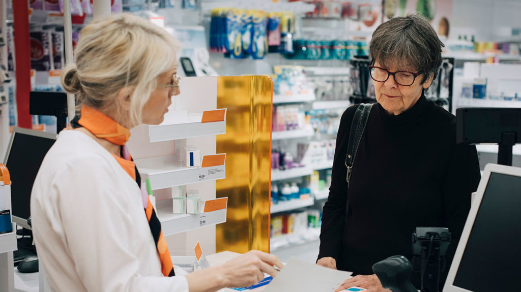 a pharmacist handing over otc anti inflammatories medication to a customer