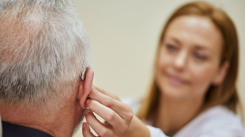 a man getting a hearing aid fitted that he got cover for on his medicare