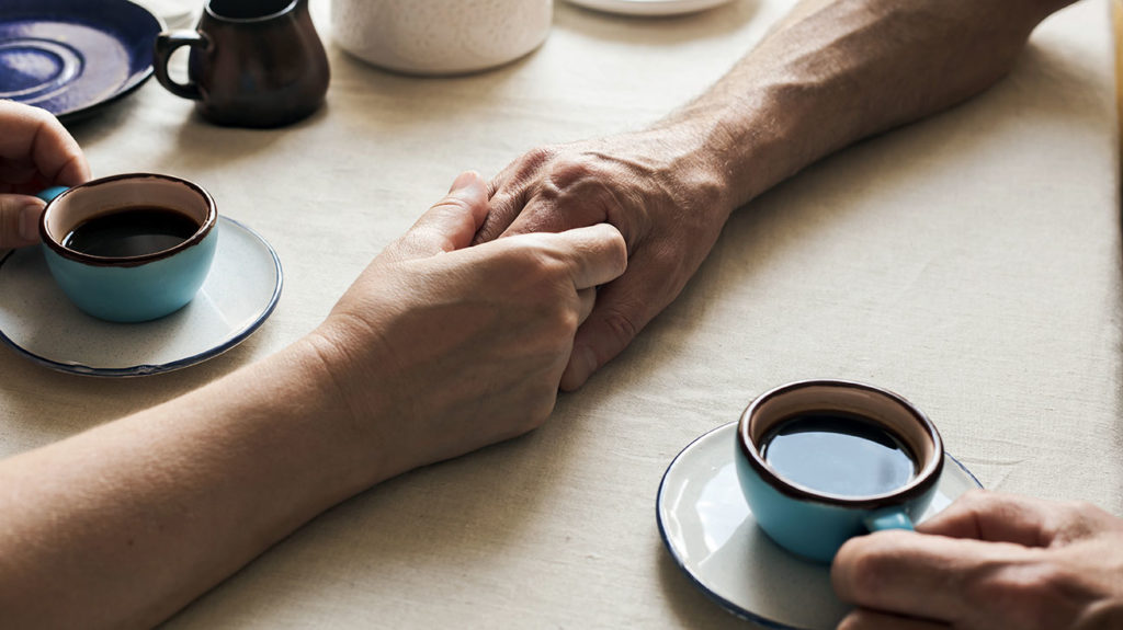 two people holding hands over a coffee table