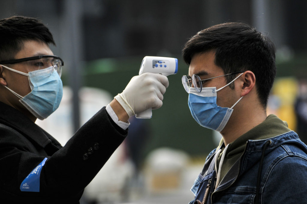 Official checking people's temperature in China