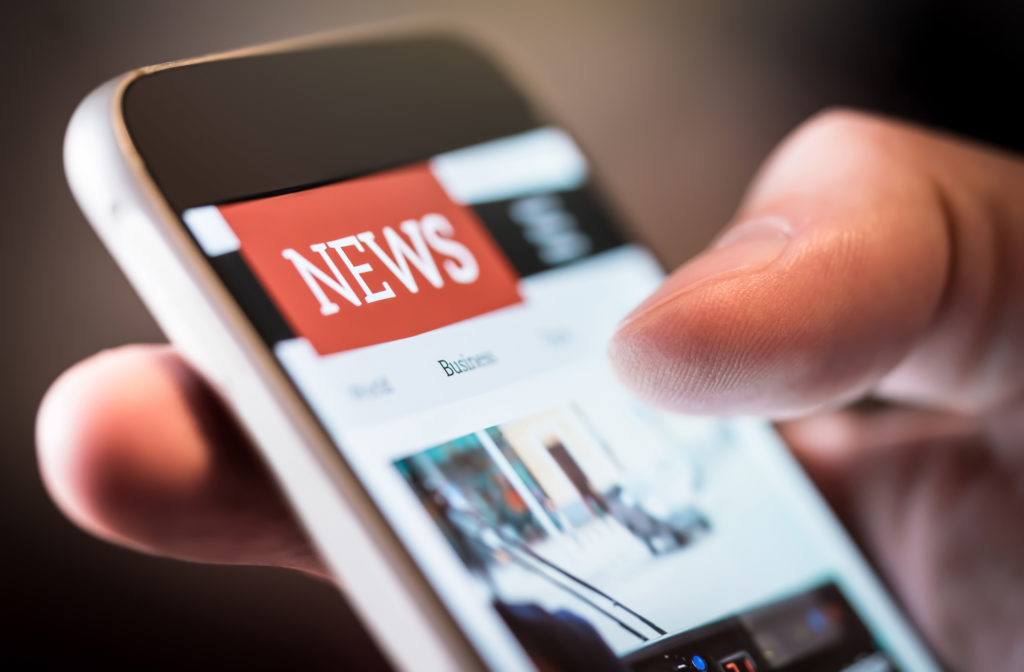 Cloe up of a hand using a smartphone to look at news