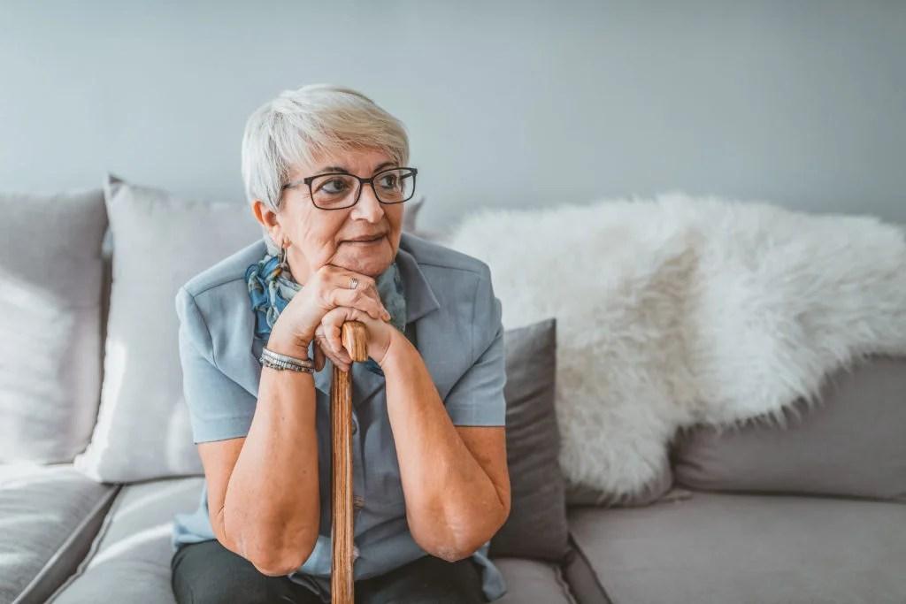 femme plus âgée se penchant sur la canne