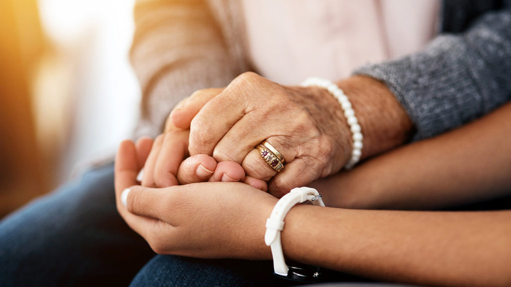 Two people holding hands to give support for vascular dementia