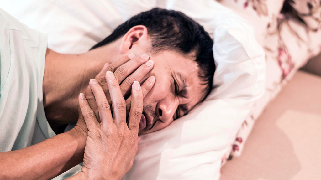 a man lying in bed and experiencing a Swollen jaw