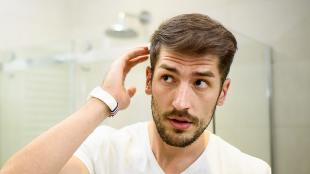 a man looking at his hair in the mirror and wondering if apple cider vinegar might help treat his dandruff