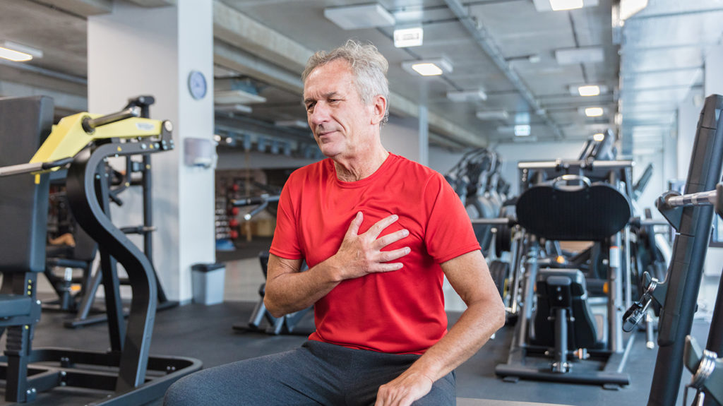a man holding his chest in the gym due to a what is atrial flutter