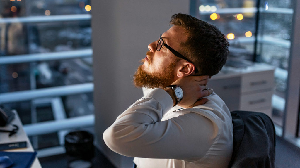 a man in an office with neck pain which is a stress symptoms