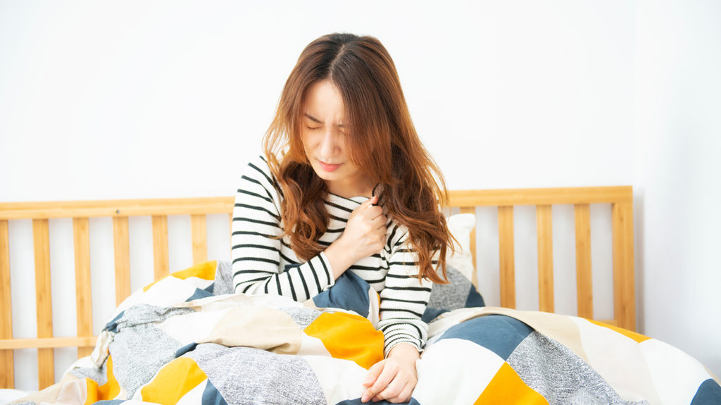 a woman holding her chest in bed because she has chest pain due to anemia