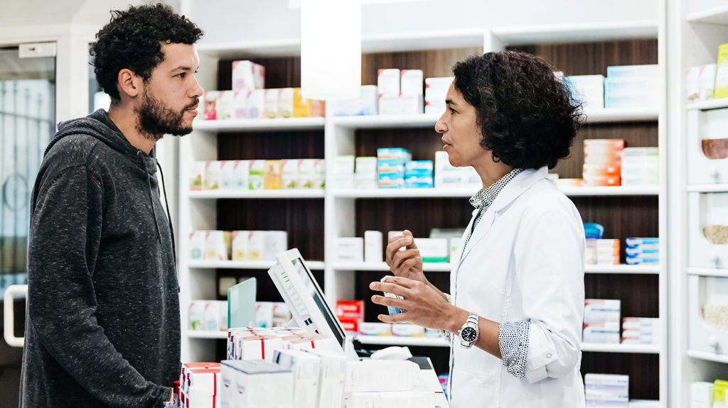 a man in a pharmacy talking to a pharmacist about Proton pump inhibitors