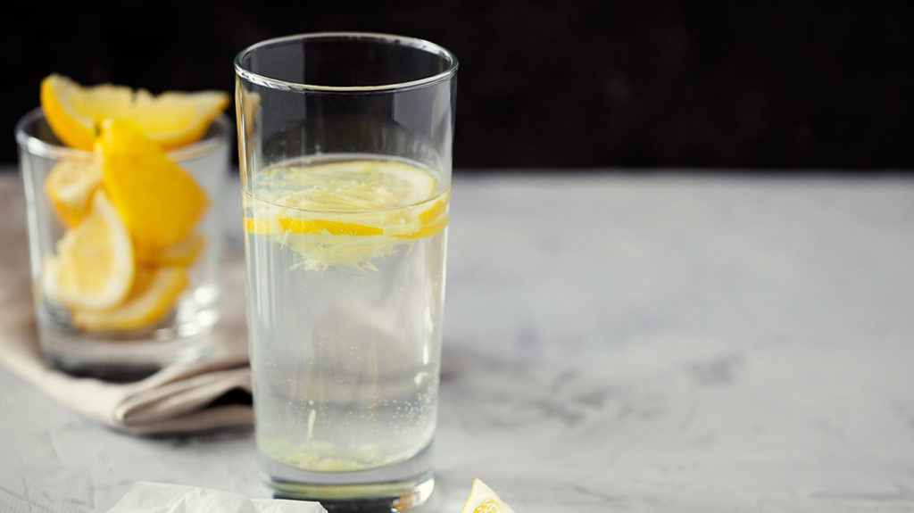 a glass of lemon water on a table