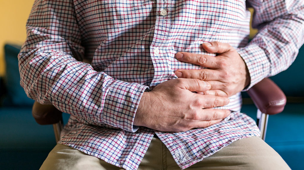 a man holding his stomach as he has pain there from intussusception