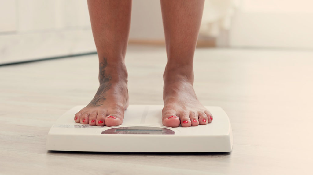 a woman standing on scales to check for Weight fluctuation