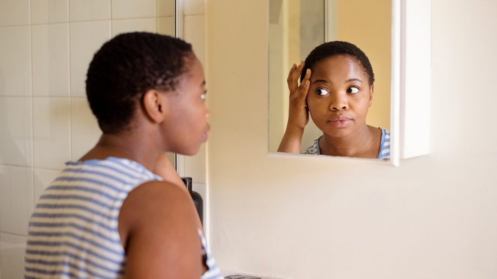 a woman with PCOS looks in the mirror to see if she has acne