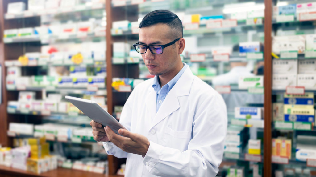 a pharmacist looking at a tablet computer
