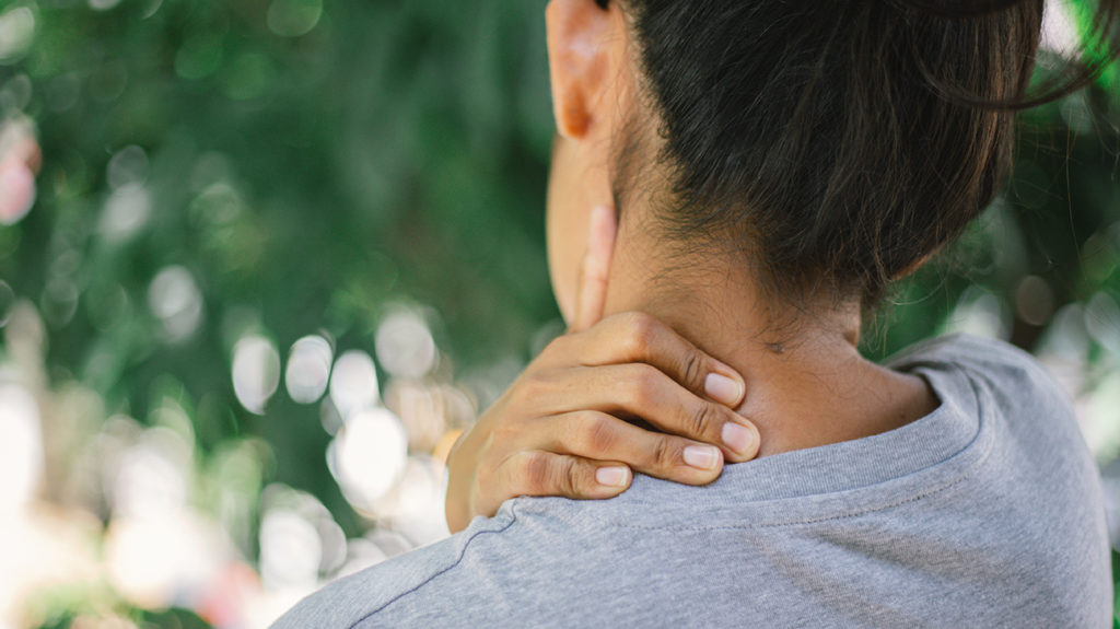 a woman holding the left side of her neck  because she has pain there