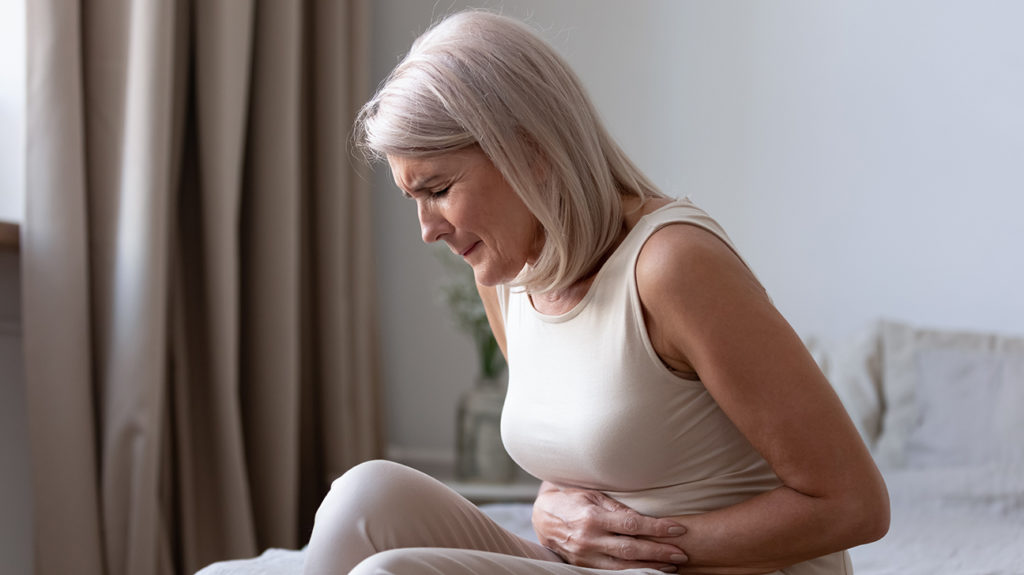 a woman holding her stomach because there is pain there from a burst appendix