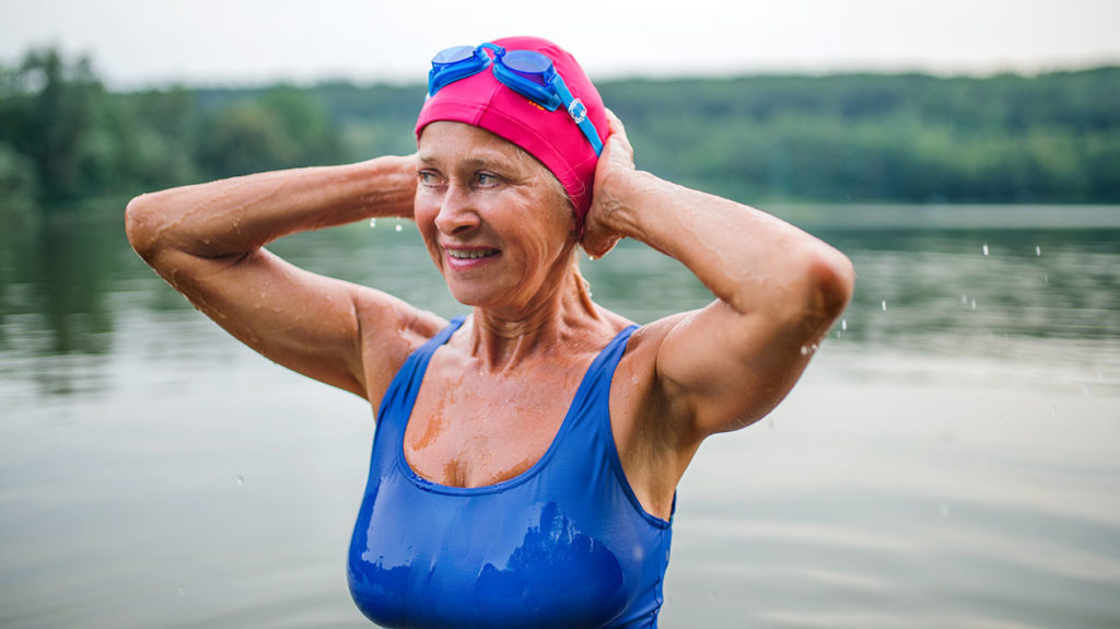 a woman having a swim outdoors to increase her basal metabolic rate