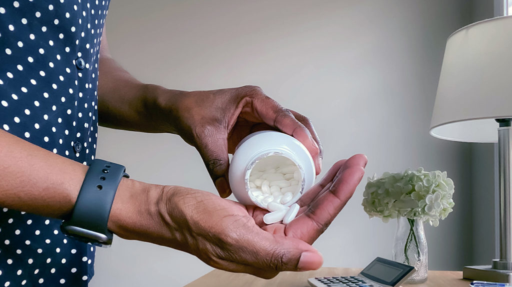 a woman pouring aspirin into her hand that she is using for treating acne