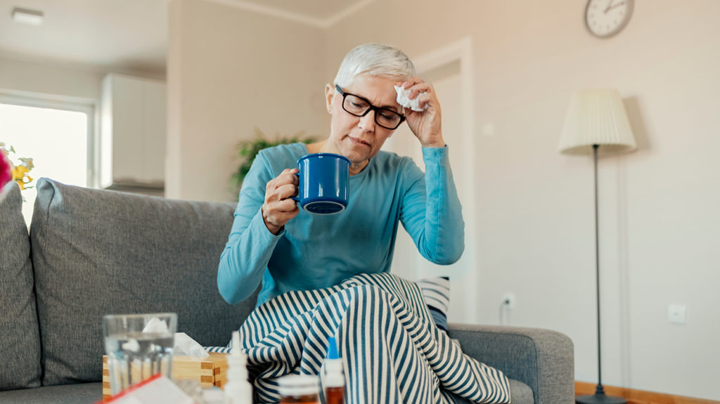 an ill woman at home experiencing covid-19 symptoms