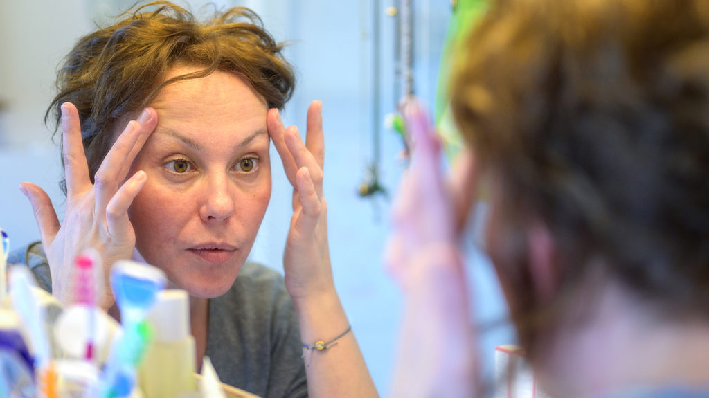 a woman looking in the mirror and checking for a pimple on the eyebrow