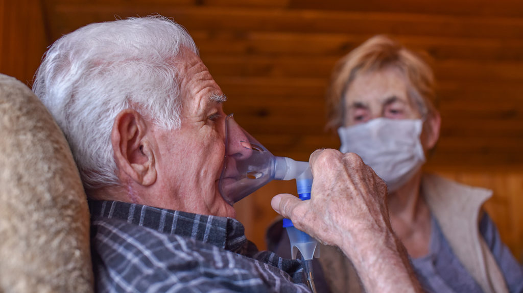 a man with COPD breathing into a mask and staying at home because of COVID-19